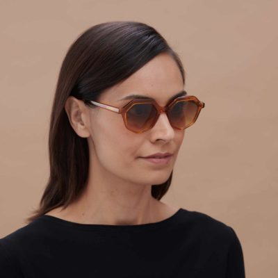 Chica con gafa de sol de diseño sostenible color caramelo